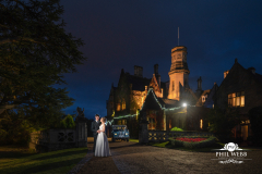 bride and groom with land rover outside manor by the lake at night