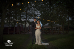 bride and groom under fairy lights at their wedding