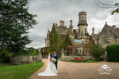 bride and groom outside manor by the lake