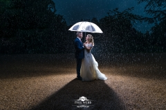 wedding pictures manor by the lake bride groom rain umbrella