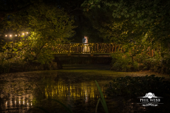bride and groom on bridge at manor by the lake at night