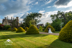 bride and groom in the grounds of manor by the lake