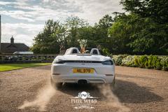 bride and groom in fast Porsche