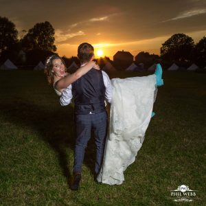 groom carrying his bride into a cotswold sunset