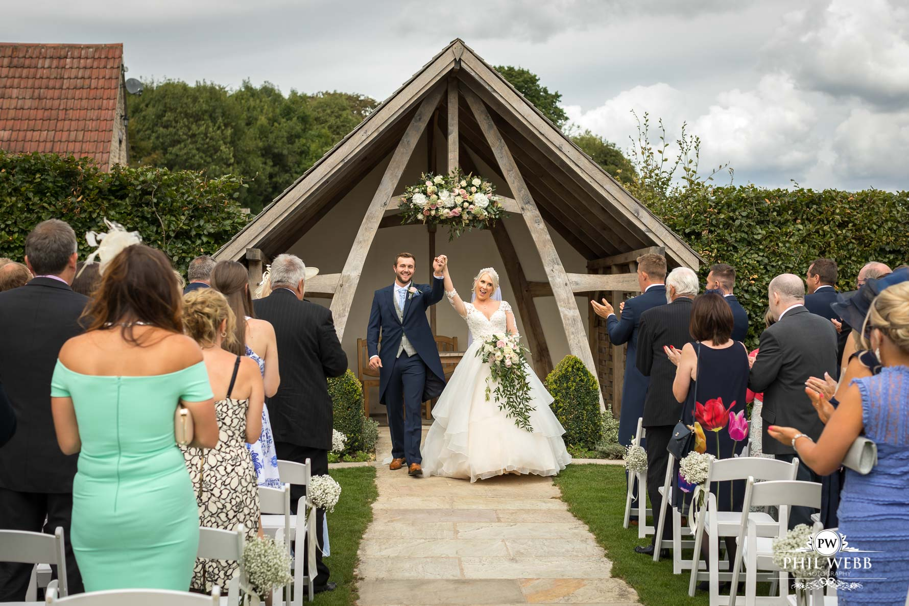 bride and groom walking down the aisle celebrating at Kingscote Barn outdoor wedding ceremony