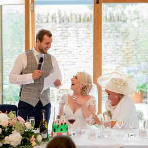 groom doing his speech at Kingscote Barn with his bride laughing