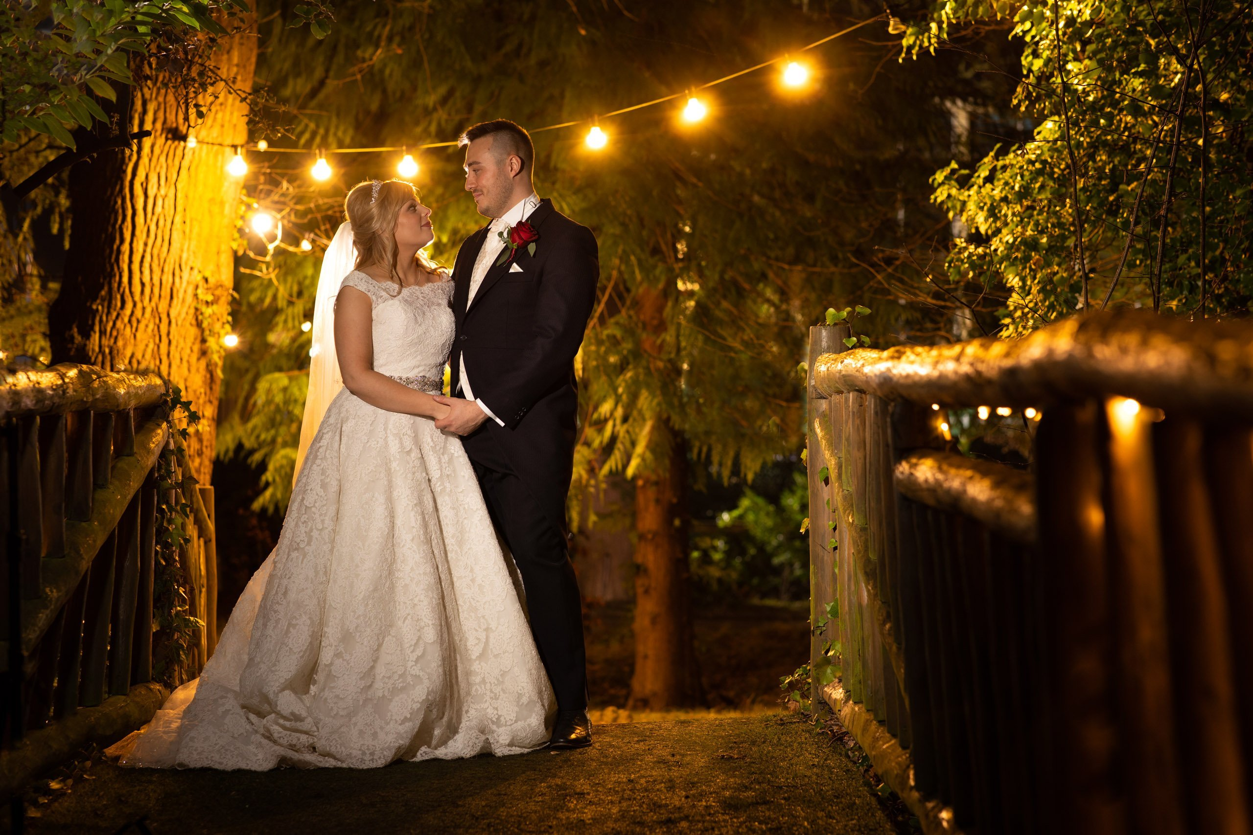 manor by the lake wedding picture bride and groom on bridge at night