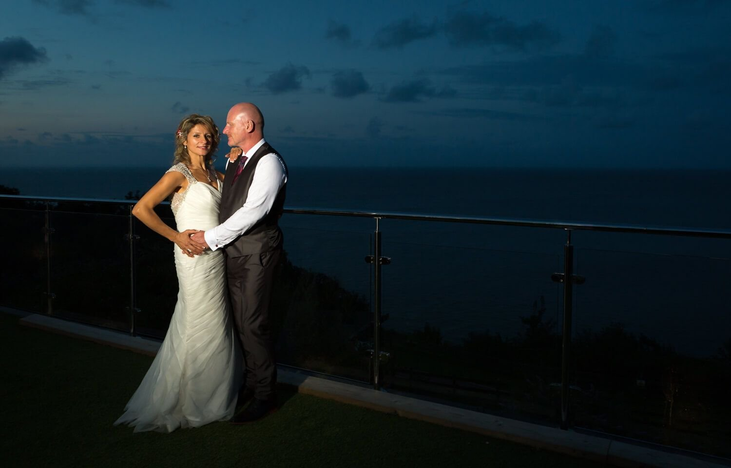 bride and groom next to the sea at sunset