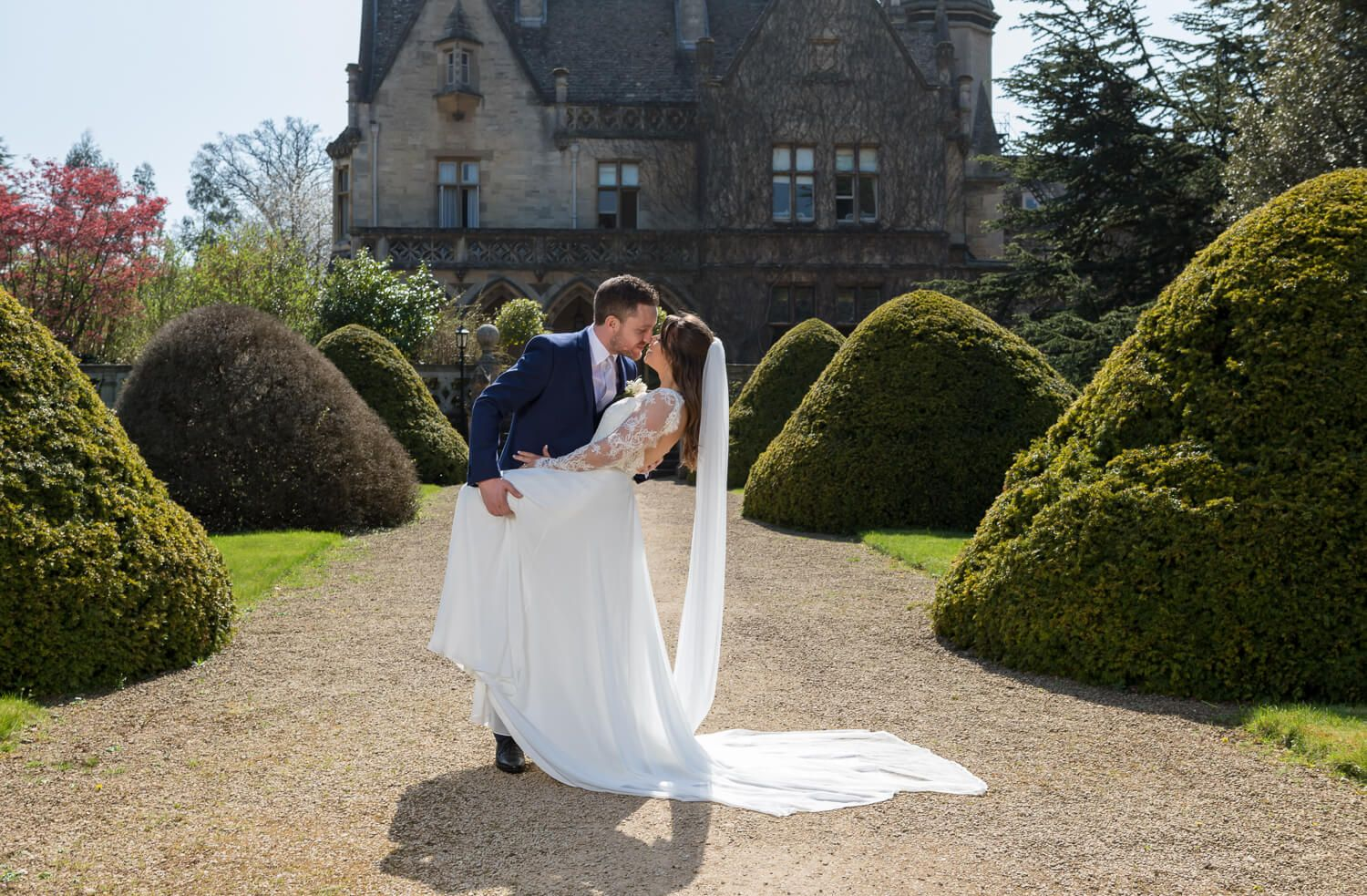 bride and groom kissing at manor by the lake