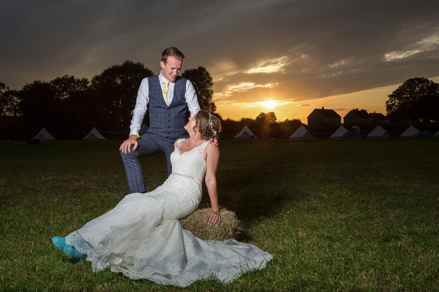 bride and groom on hay bail at sunset