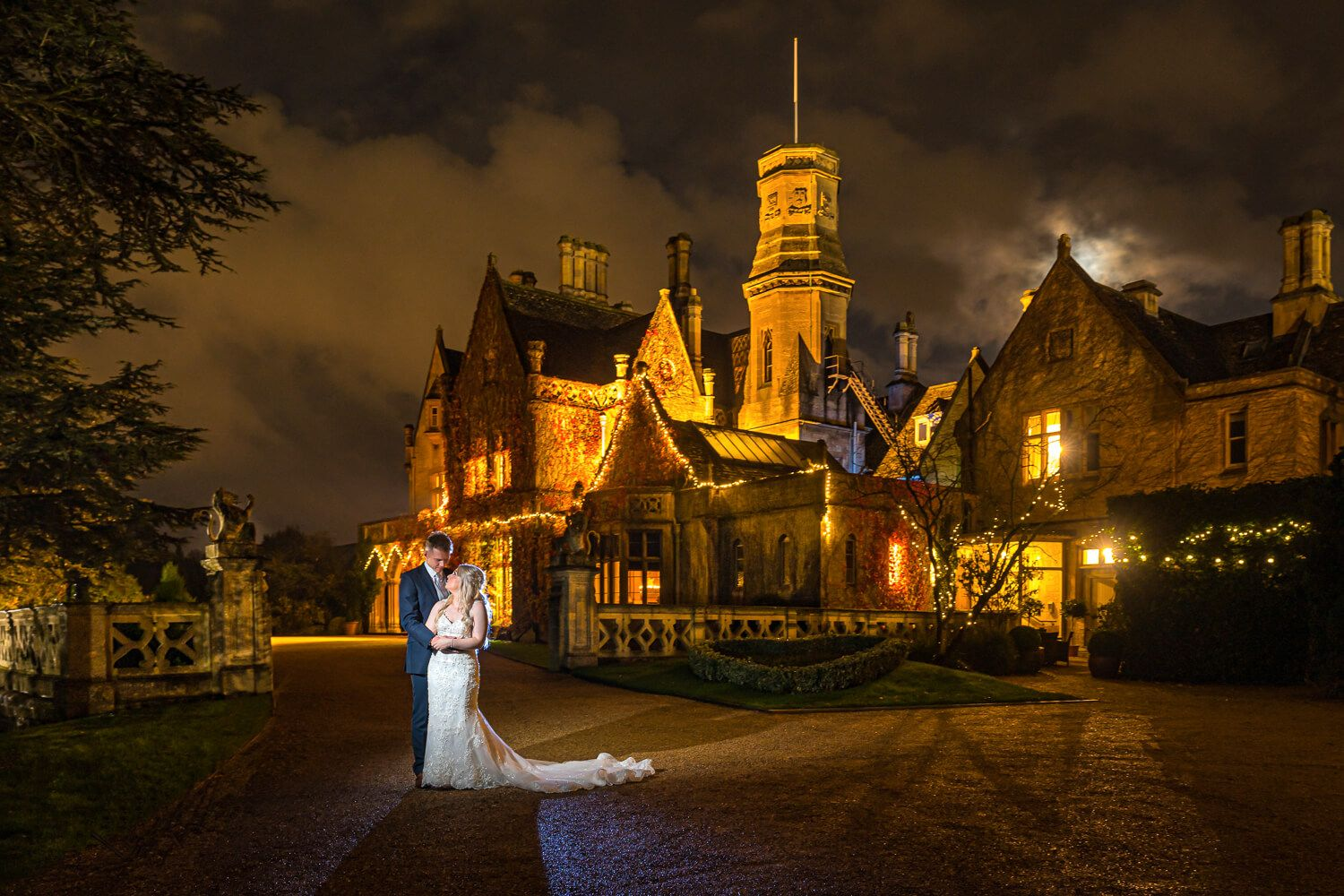 bride and groom at night in front of manor by the lake
