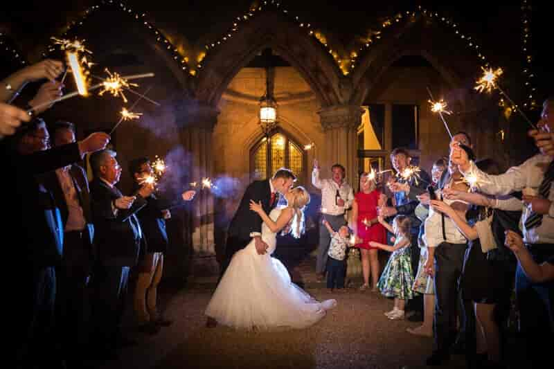 Bride, groom and guests with sparklers outside manor by the lake