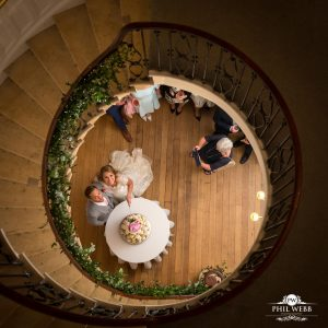bride and groom at bottom of spiral staircase cutting their wedding cake