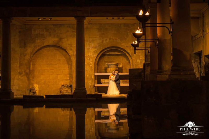 bride and groom at Roman Baths in Bath next to the water