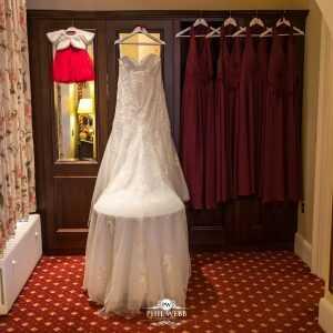wedding dress hung up with bridesmaids dresses