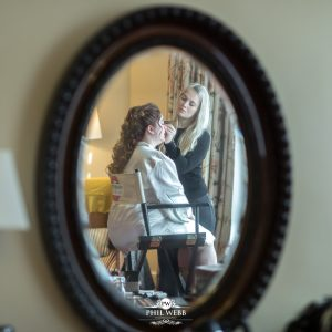picture of bride in the mirror having her make up applied